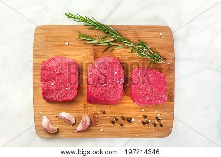 Three slices of raw meat, beef fillet, shot from above on a white marble texture with a sprig of rosemary, garlic cloves, salt, and pepper