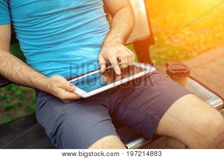 Man sitting on a bench and using a digital tablet. Men's hands closeup. Sun flare