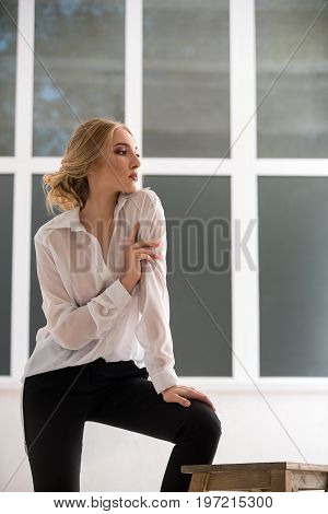 Woman wearing sexy white shirt studio portrait with large window on a background