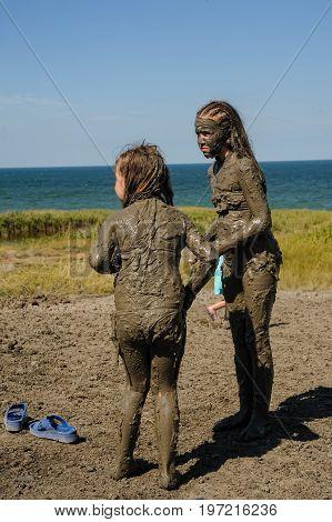 Kuchugury, Russia - July 16, 2017: Azov scorching heat mud volcano. Girls take procedures with healing mud