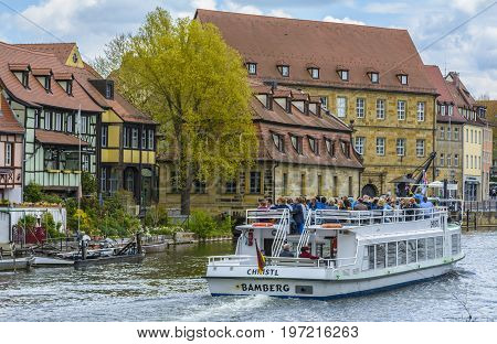 Old buildings architecture with Christl boat in foreground on Linker Regnitz river on April 26 2015 in Bamberg Germany.