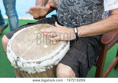 drum, percussion instruments and culture concept - closeup on hands of musician playing with african djembe, summer outdoors concert performance, ethnic rhythm performance, selective focus