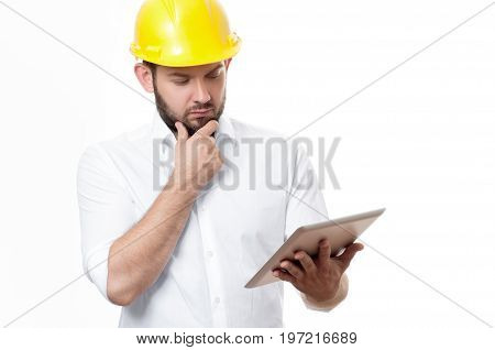 Contractor In Yellow Builder Helmet Working On A Project With Tablet.