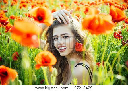 poppy seed and happy girl with long curly hair in red flower field with green stem on natural background summer spring drug and love intoxication opium