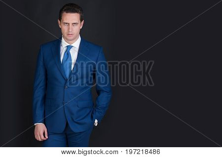 Man confident businessman or handsome manager with fashionable hair haircut posing in stylish blue formal suit white shirt and tie on grey background. Business fashion copy space