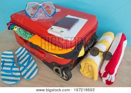 Suitcase with different things prepared for travel. Red suitcase with clothes and personal things packed for travelling