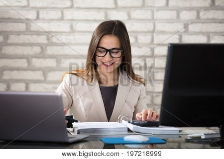 A Young Smiling Accountant Calculating Invoice Using Calculator In Office