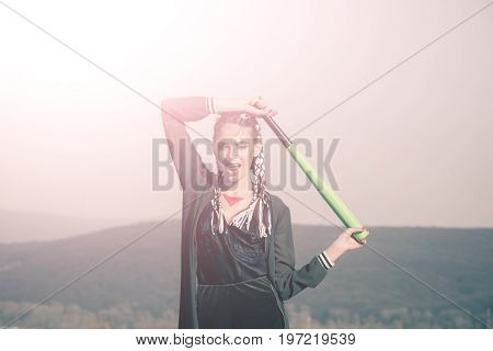 Sport or criminal girl outdoor. Hooligan on blue sky. Bandit gang and conflict. Beauty and fashion. Woman smiling with baseball bat.