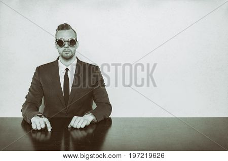 Portrait of businessman wearing welding punk glasses while sitting at desk against white background