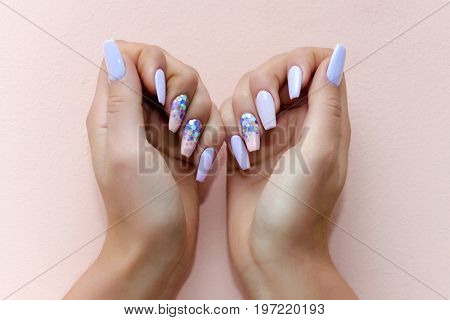 Woman show professional manicure on pink background. Nail polish on female fingers. Spa and skincare. Hands of girl with manicure. Beauty and fashion.
