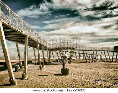 beach at the lido in venice with metal modern pier and elevated walkways with dramatic sky sea and sand out of season.