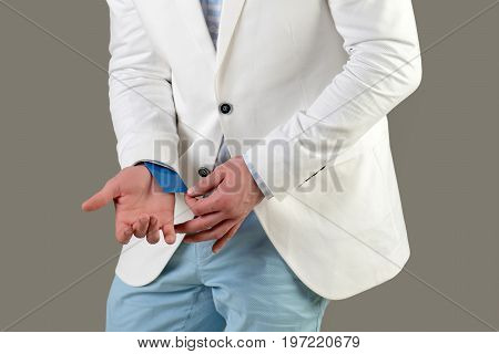 Advantage and secret trump. Ace up sleeve concept. Empty business card in cuff. Businessman in white jacket on grey background. Cheating and trick