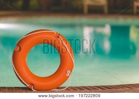 Orange lifebuoy or ring buoy on edge of swimming pool outdoors. Night scene.