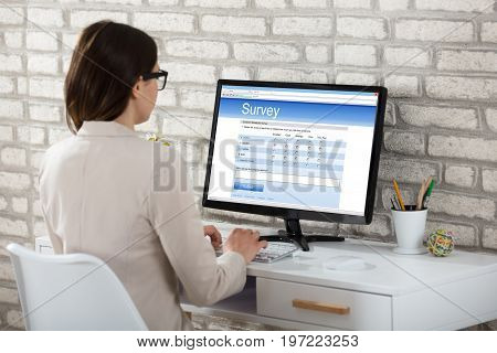 Rear View Of A Businesswoman Filling Survey Form On Computer In Office