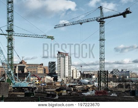 Large urban development construction site in Leeds with cranes machines mixers and building materials