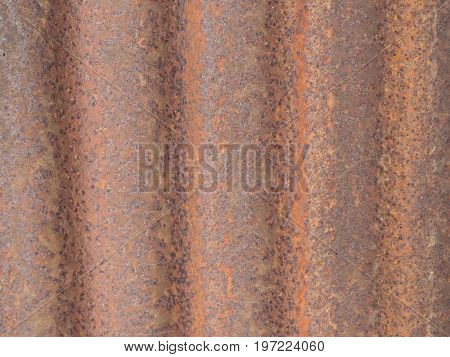 Rust background, corrugated sheet metal that has rusted out over time.