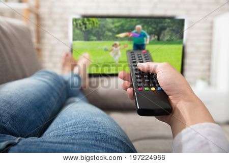 Close-up Of A Woman Changing The Channel With Remote Control While Watching Television