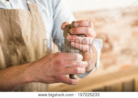 pottery, stoneware, ceramics art concept - closeup on master hands holding some piece of fireclay, young male in dirty apron work at a workshop, men hands form the future product from raw clay