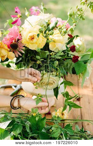 wedding, celebration, floral design, spring, nature concept - woman's hands fixing few stalks in great multicolored bouquet made of ballet pink peonies, english roses and avalanches