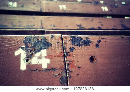 Number Fourteen Painted On An Old Wooden Seat.