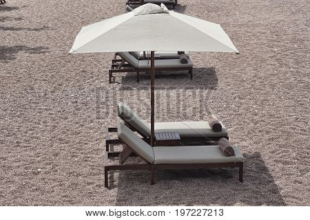 Two Sunbeds And Umbrella With Small Table