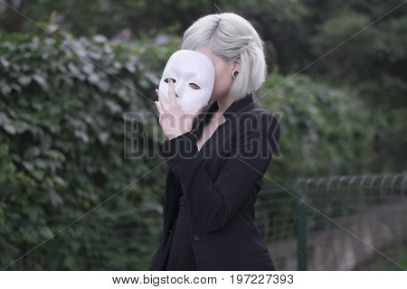 Young blond girl taking off a mask. Pretending to be someone else concept. outdoors