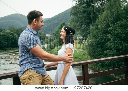 man with woman stands on the bridge across the river in mountains