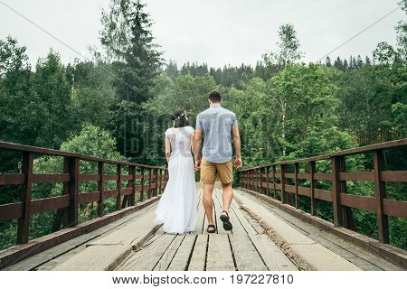 man with woman stands on the bridge in mountains