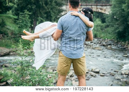man taking woman in white dress on his arms near mountains river