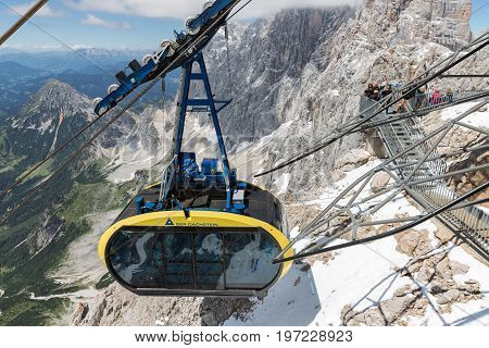 DACHSTEIN MOUNTAINS AUSTRIA - JULY 17 2017: Cable car with tourists approaching the Dachstein glacier mountain station in Austria