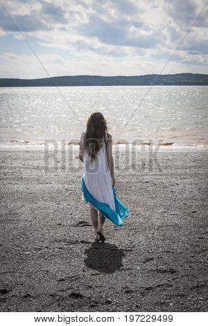 Woman Strolling Along Black Beach, Lorneville, New Brunswick, In Atlantic Canada