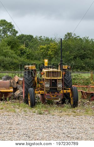 Old yellow cabless tractor on waste ground.