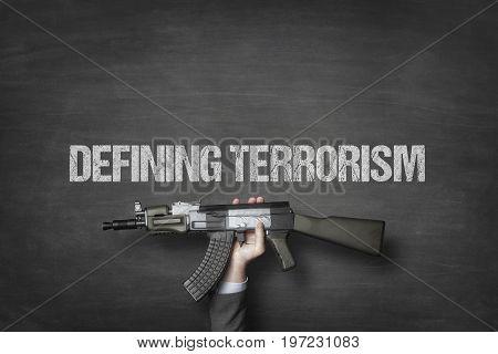 Cropped image of businessman's hand holding machine gun under defining terrorism text on blackboard