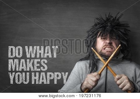 Funky man with long hair holding drumsticks by do what makes you happy text on blackboard