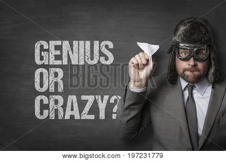 Portrait of businessman wearing vintage aviator hat and glasses while holding paper plane by genius or crazy text on blackboard