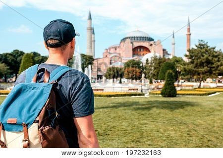 A traveling man with a backpack in Sultanahmet Square near the famous Aya Sofia mosque in Istanbul in Turkey. Travel, sightseeing.
