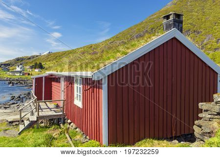 Red Classic Norwegian Rorbu fishing hut with sod roof on Lofoten islands, Norwegian traditional type of house used by fishermen