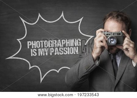 Businessman photographing through retro camera by photography is my passion text on blackboard