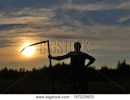 Silhouette of a man with a scythe against the sun in the evening in the field