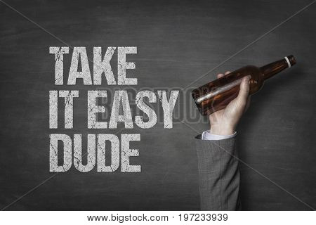 Cropped image of businessman's hand holding alcohol bottle by take it easy dude text on blackboard