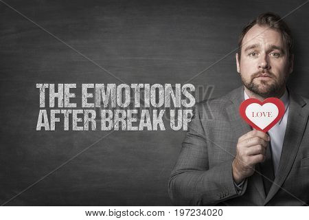 Portrait of sad businessman holding heart shape by the emotions after breakup text on blackboard