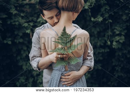 Stylish Hipster Bride And Groom Embracing In Green Leaves Forest. Man Kissing Woman Neck. Couple Emb