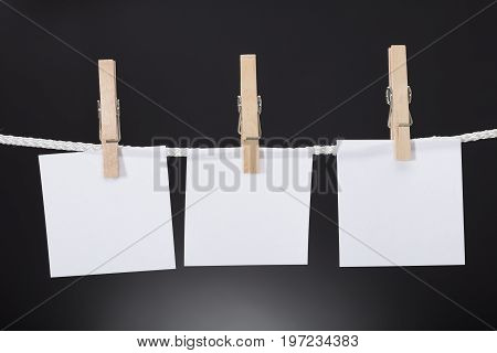 Closeup of white paper cards hanging on rope attached with clothespins against black background