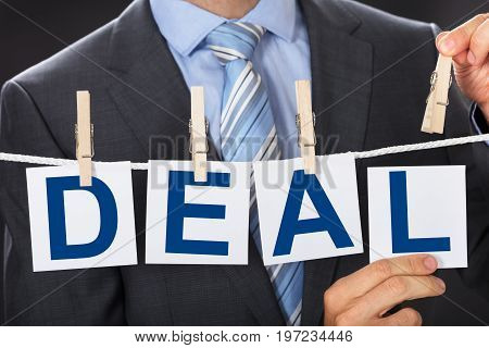 Closeup midsection of businessman pinning DEAL cards on clothesline
