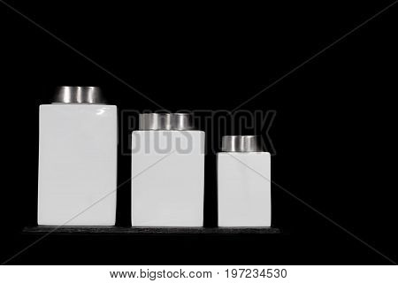 Modern minimalist kitchen storage jars. Square white ceramic canisters in modern design. Set of three sizes on slate coaster against black background with copy and label space.