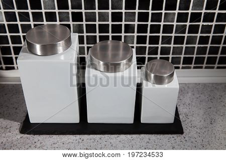 Modern square design storage jars on work surface in black and white tiled kitchen.