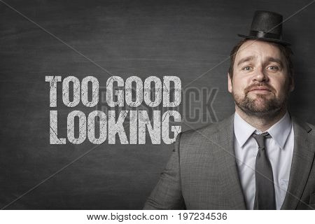 Portrait of confident businessman with small tophat standing by too good looking text on blackboard