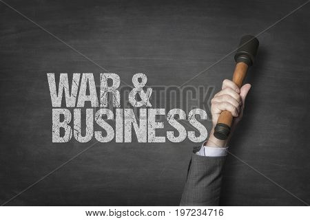 Cropped image of businessman's hand holding stick grenade by war and business text on blackboard