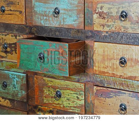 pulled drawer on old wooden colorful dresser with iron hitch