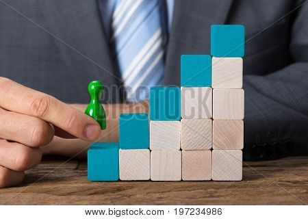 Closeup of businessman moving pawn upstairs made of wooden blocks on table
